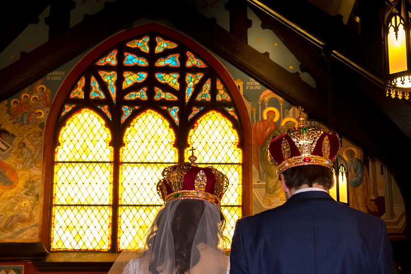 Stunning light coming through the stain-glass window and illumining the couple at Christ the Savior Orthodox Church, Chicago, IL.