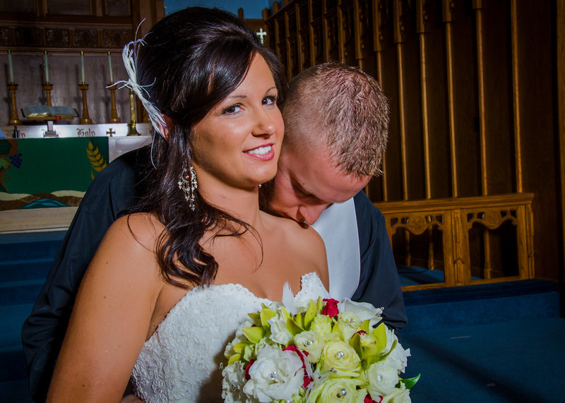 Wedding photo of groom kissing brides shoulder