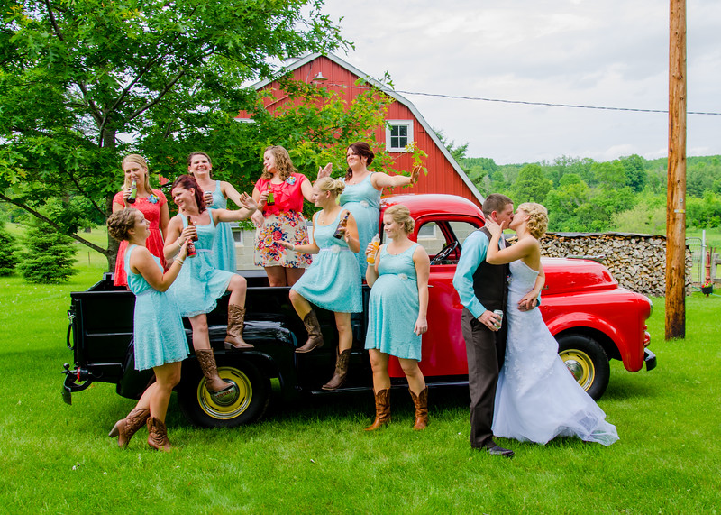 Bride and groom with bridesmaids in old truck
