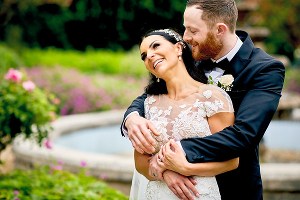 Groom holds his beautiful bride in his arms