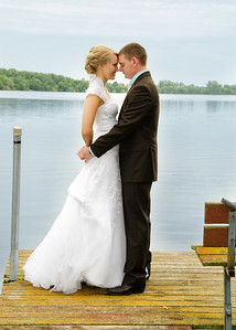 Bride and groom on dock at lake