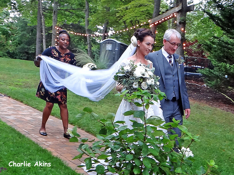 The bride and her father are walking to the dock.