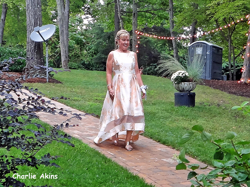 The mother of the bride is walking to her seat.