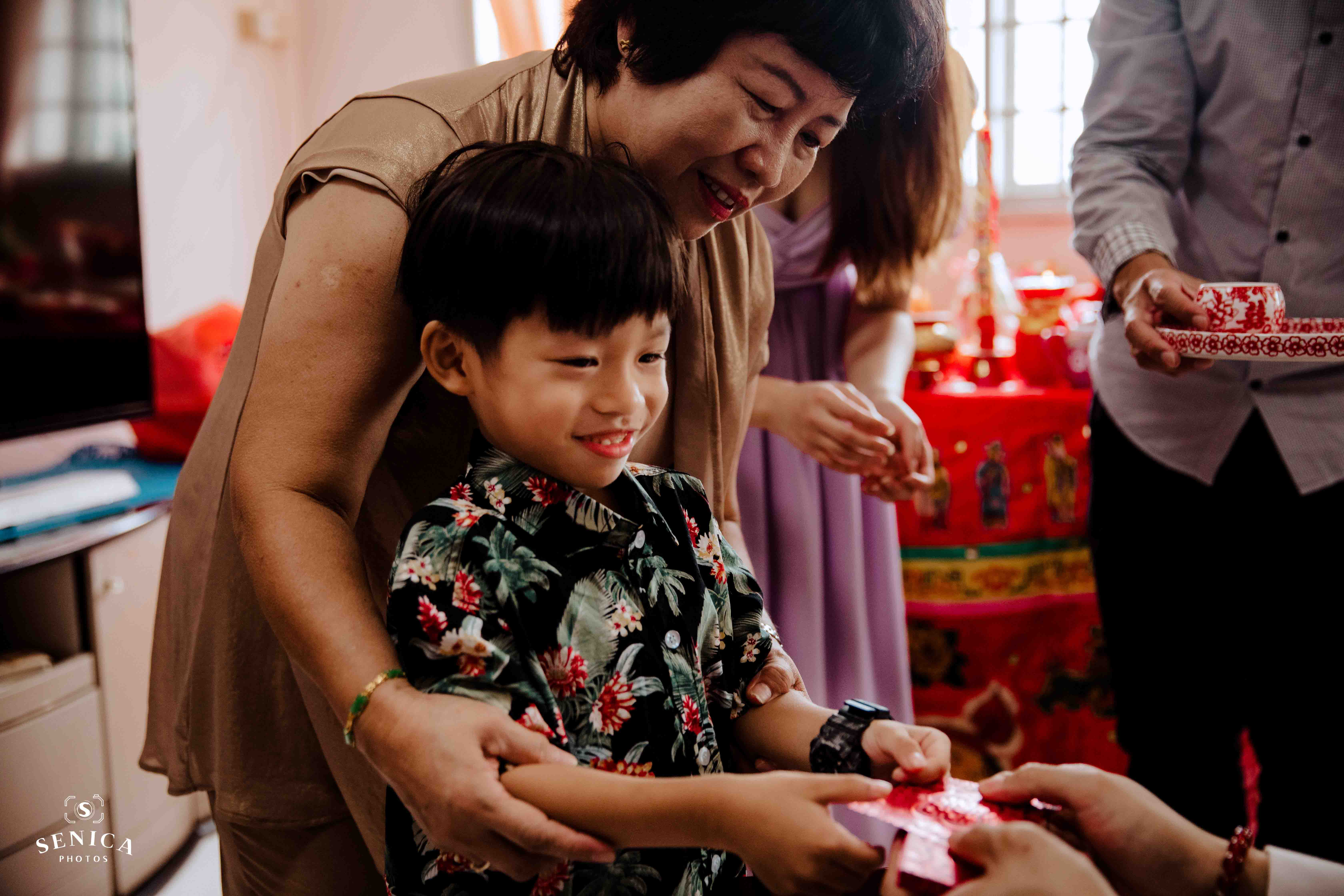 Child receiving red packet from the couple after serving tea to them