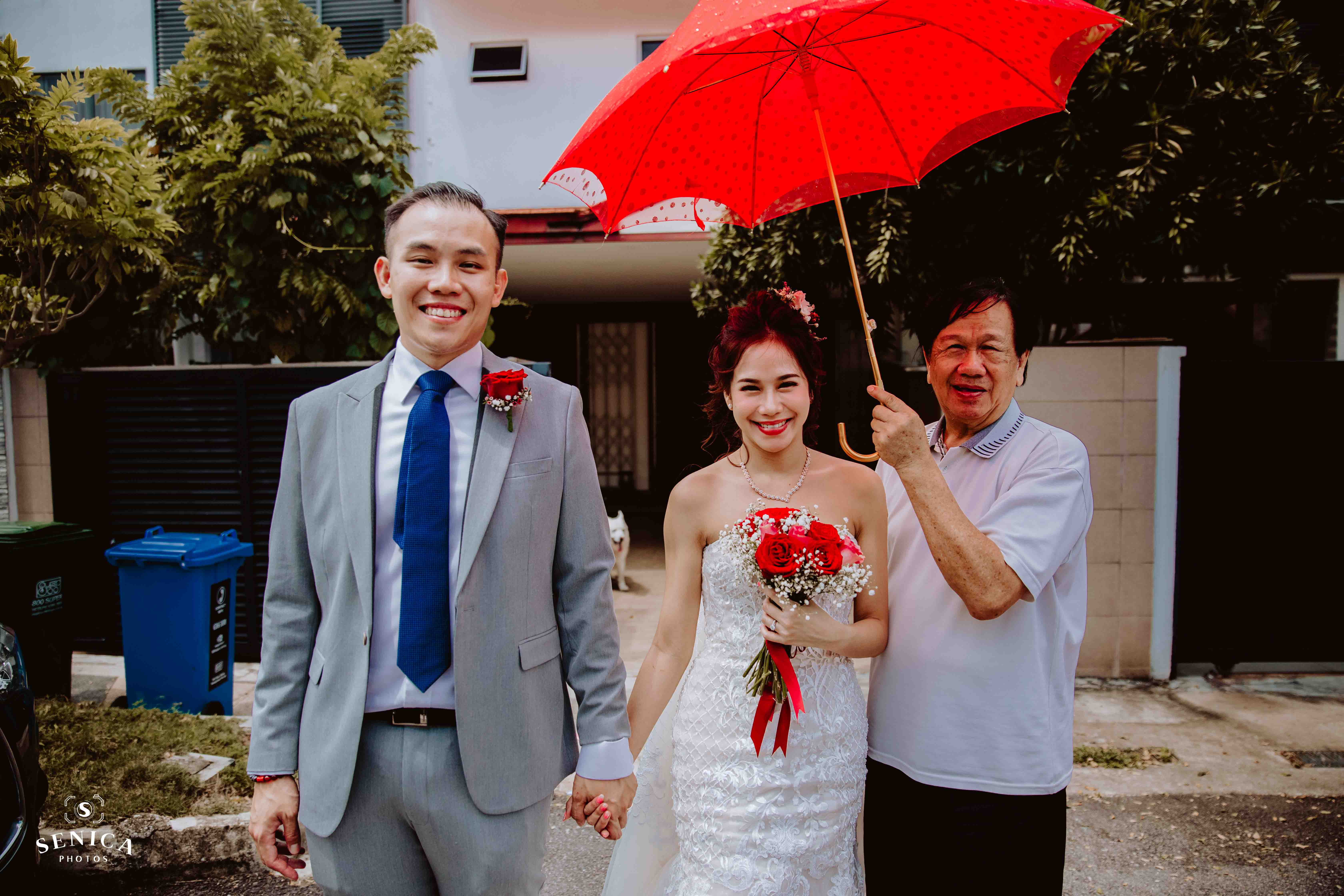 Bride's father holding umbrella over her while groom leads her to the bridal car