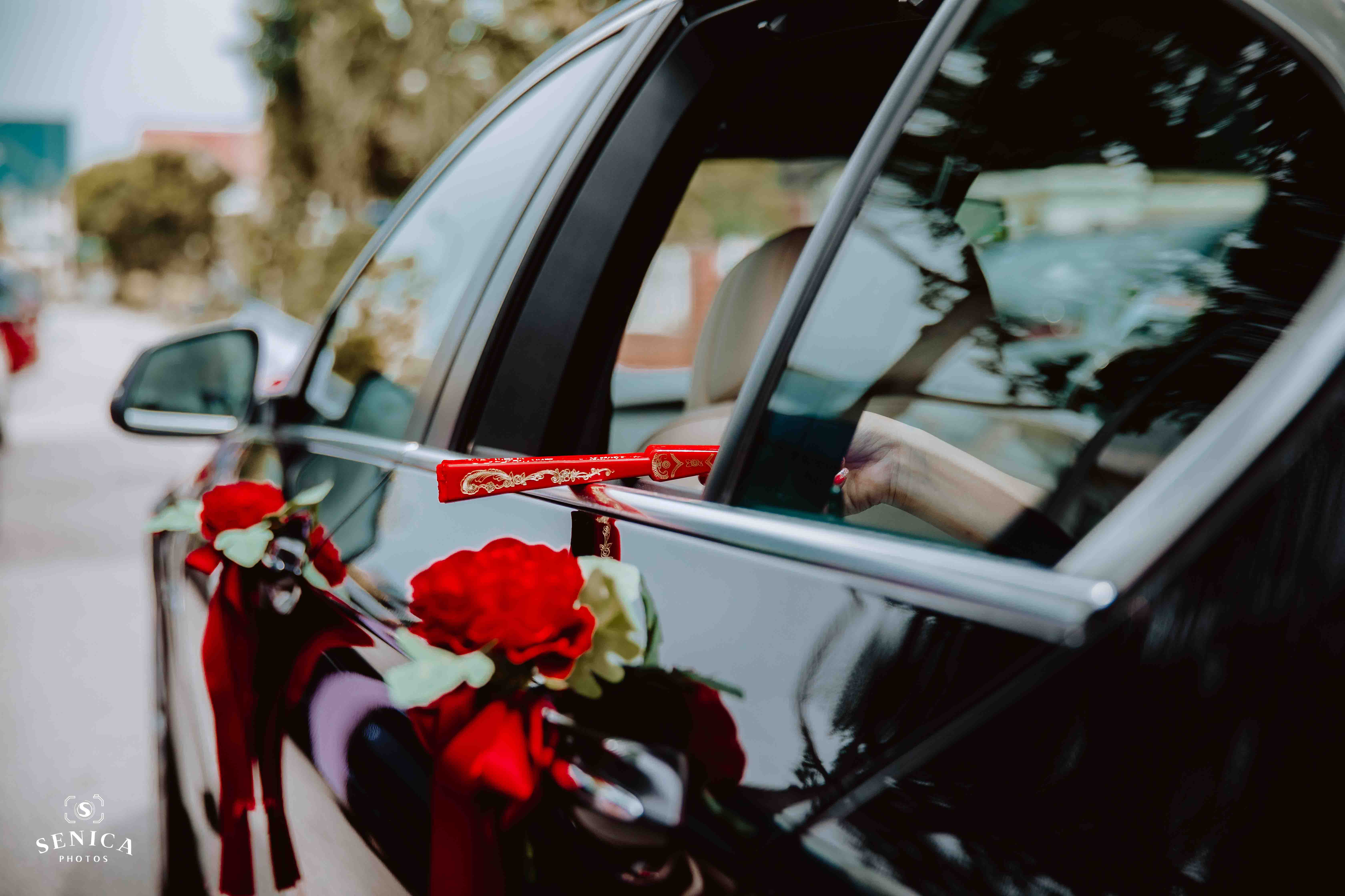 Bride throwing red fan out of the car window