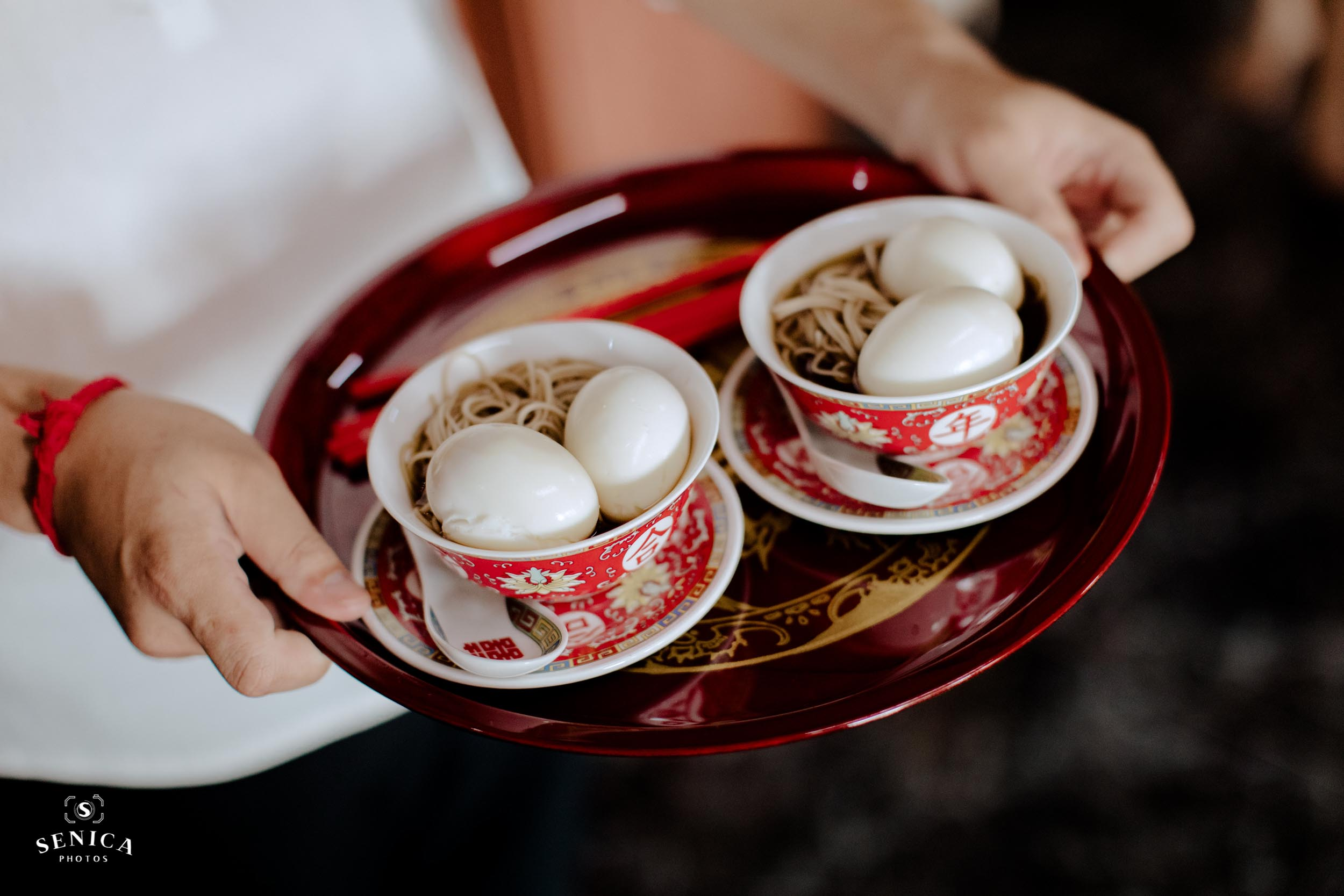 two bowls of mee sua and hard boiled eggs served on a large red plate