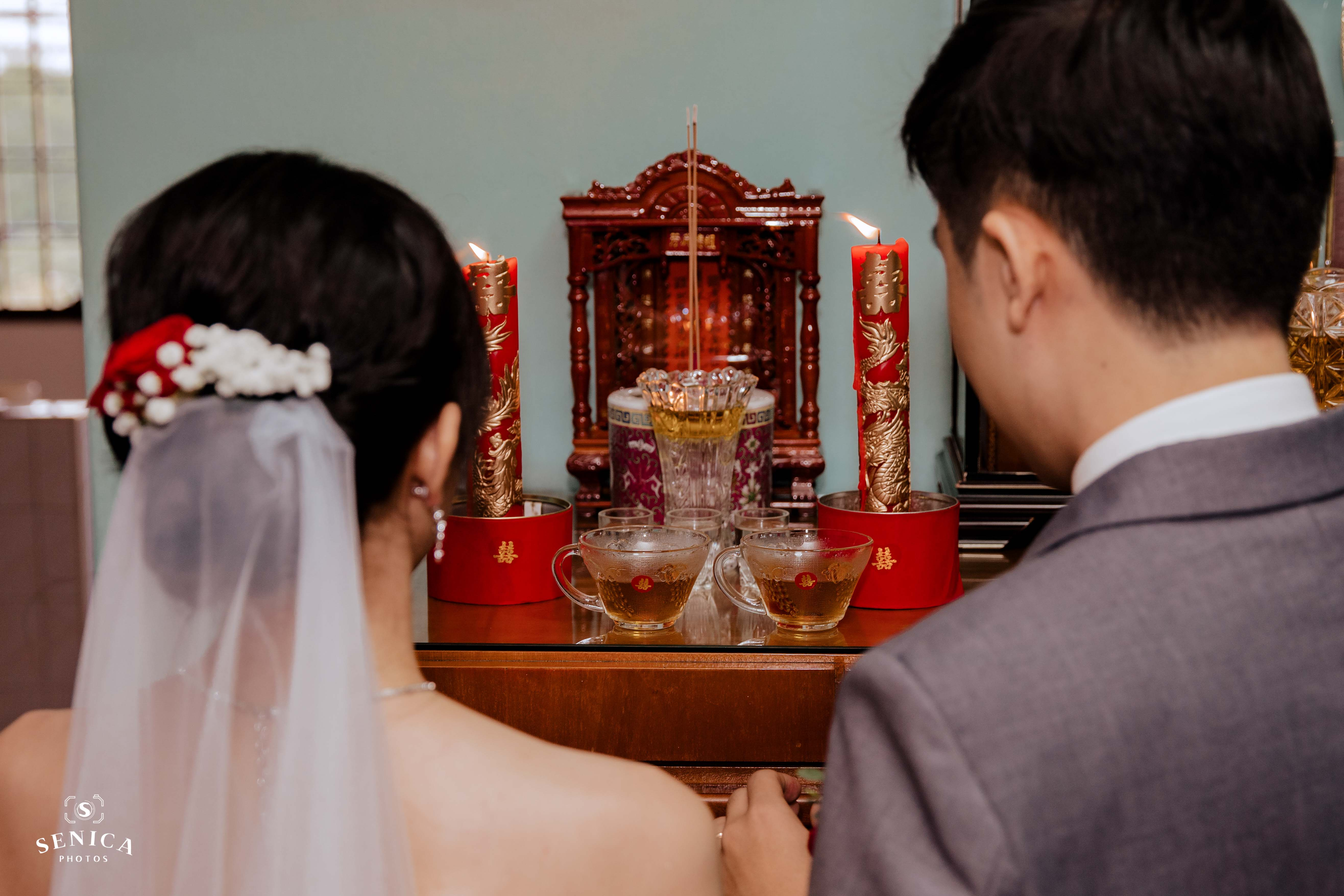 bride and groom praying at the altar with dragon and phoenix candlesticks