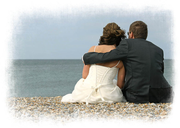 A couple on their wedding day on Cley Beach following a wedding ceremony at Cley Windmill