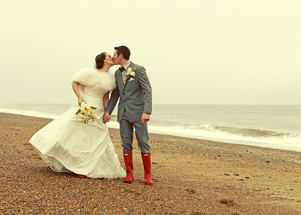 A bride and groom on Cley Beach at a winter wedding before returning to Cley Windmill for their wedding breakfast
