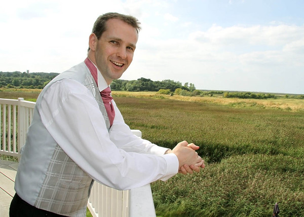Before the ceremony a groom enjoying the views at Cley Windmill