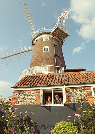 A bride and groom looking out at Cley Windmill