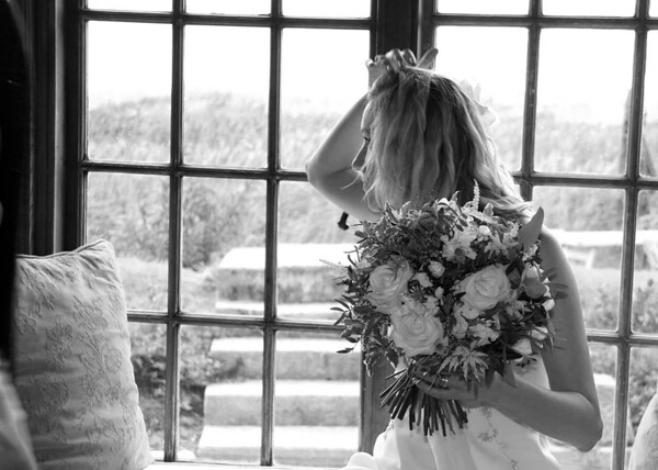 A bride at Cley Windmill sat in the window seat taking a couple of minutes out before their wedding breakfast
