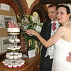 A bride and groom cutting their cake during their wedding reception at Cley Windmill