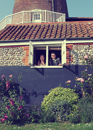 A bride and groom peeping out of a window at Cley Windmill on their wedding day
