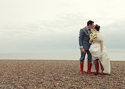 A bride and groom at their winter wedding on Cley Beach in their wellies after their wedding ceremony at Cley Windmill