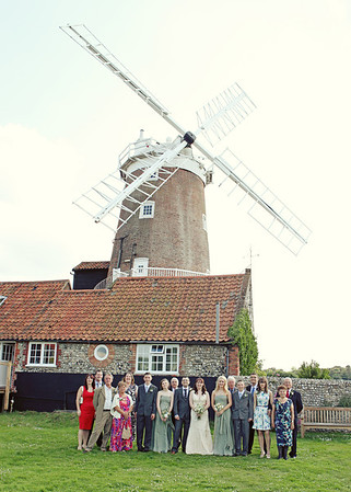 A formal wedding party group shot at Cley Windmill