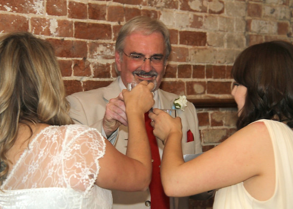 A dad and his daughters after his speech at a wedding at Dairy Barns
