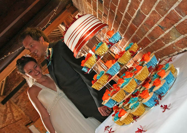 A bride and groom with their cake at Dairy Barns