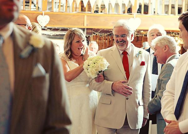 A happy bride walking and waving all the way down the aisle at Dairy Barns