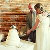 A bride and groom cutting their wedding cake at their wedding reception at Dairy Barns