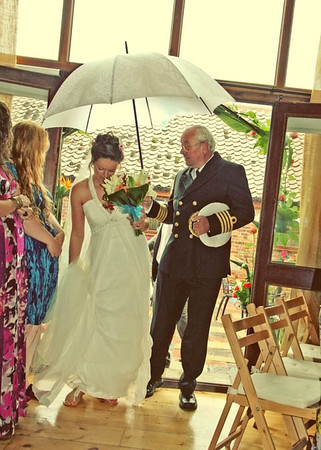 A bride arriving with her dad in the rain for her wedding ceremony at Dairy Barns
