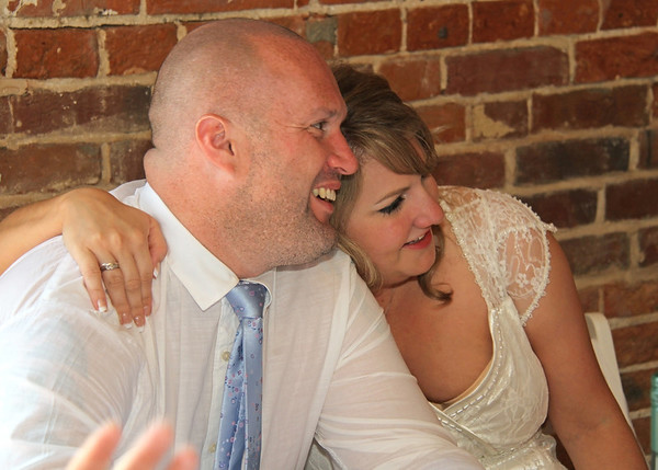 A bride and groom listening to the bestman's speech at Dairy Barns