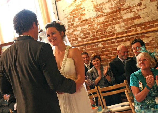 A Bride and groom during their wedding ceremony at Dairy Barns