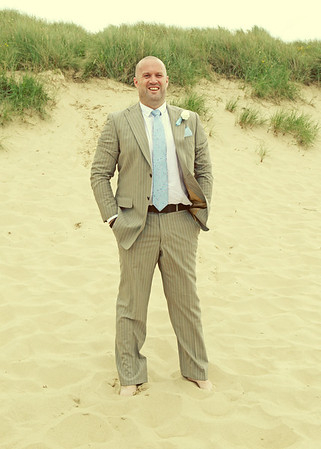 A groom down on Sea Palling beach before going back to Dairy Barns for their wedding reception