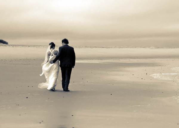 A bride and groom on Sea Palling beach after their wedding ceremony at Dairy Barns