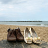 A bride and groom's shoes down on Sea Palling beach before going back to Dairy Barns for their wedding reception