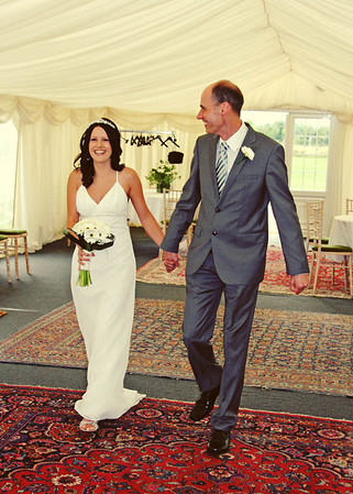 An eager bride and a proud dad coming in through the marquee to the ceremony