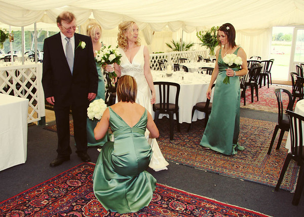 Bridesmaids helping with the last minute touches to the bride before going in for the ceremony at Elms Barn