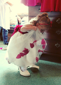 A little flowergirl trying on the brides shoes during getting ready at Glemham Hall on a wedding day