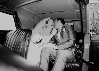 A bride and groom in a vintage car on their winter wedding day at Haughley Park Barn