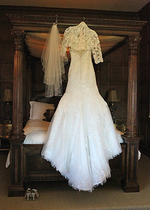 A brides dress hanging in Hengrave Hall on a wedding day