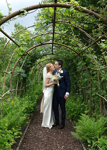A bride and groom in the gardens at Otley Hall on their summer wedding day