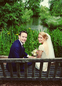 A bride and groom in the gardens at Otley Hall on their summer wedding day (look at the rain on the water behind them!)