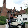 A bride and groom on their wedding day with a vintage car outside of Otley Hall