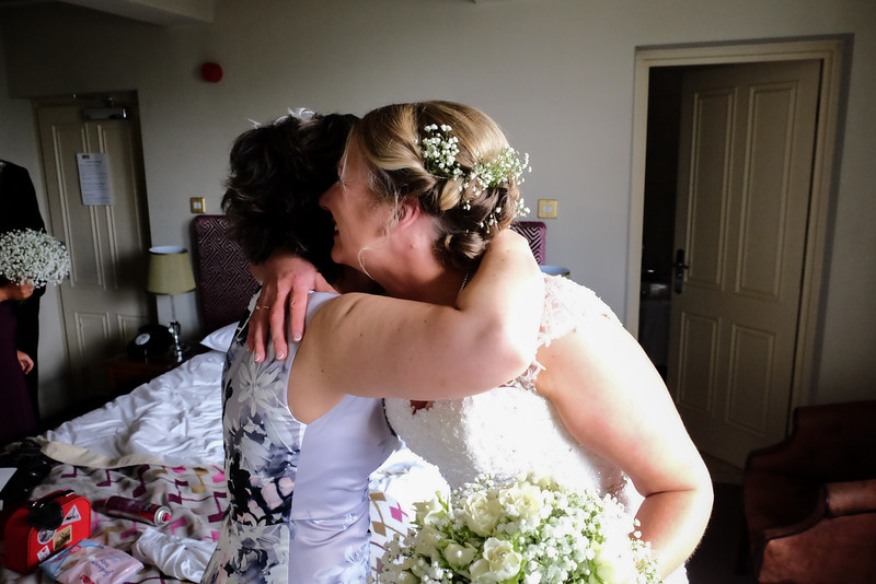 Bride hugging a bridesmaid.