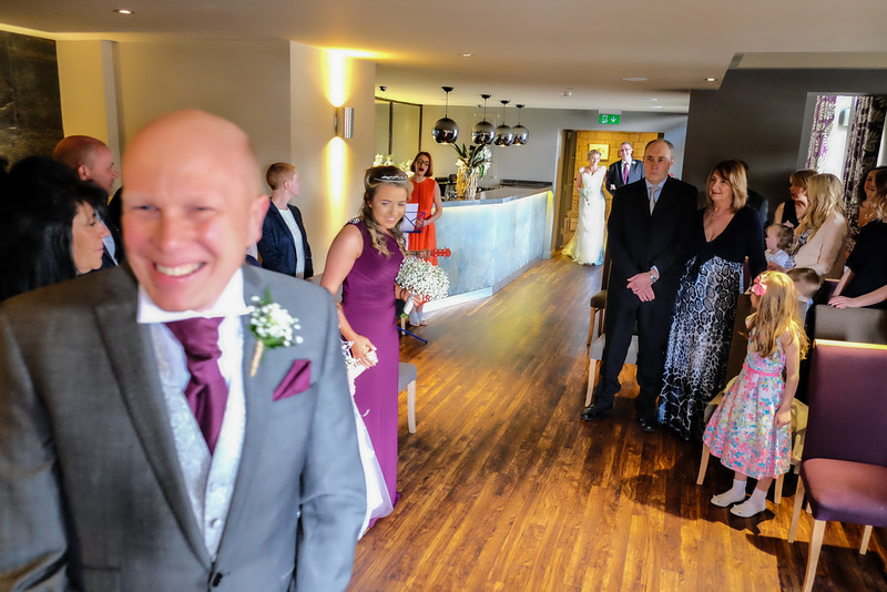 Groom smiling as Bride arrives.
