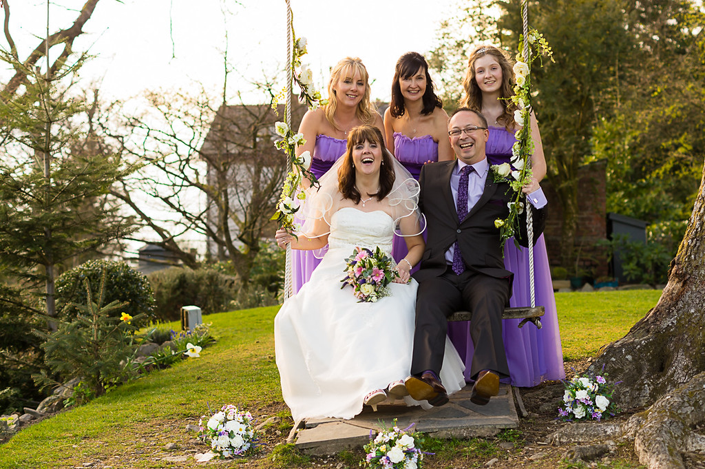 Bride and Groom on a swing with the bridesmaids