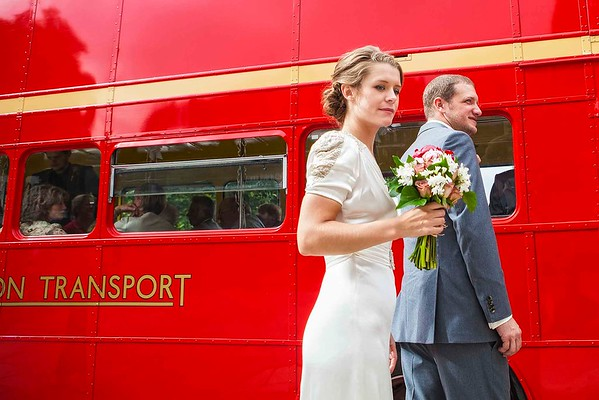 bride and groom getting onto a red wedding bus