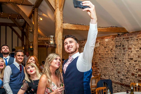 wedding guest taking a selfie with other guests