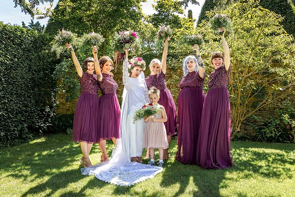 bride and bridesmaids holding up flowers