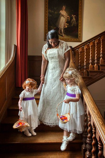hindu bride walking down stairs with her flower girls
