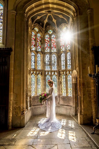 bride in front of the oriel stained glass window