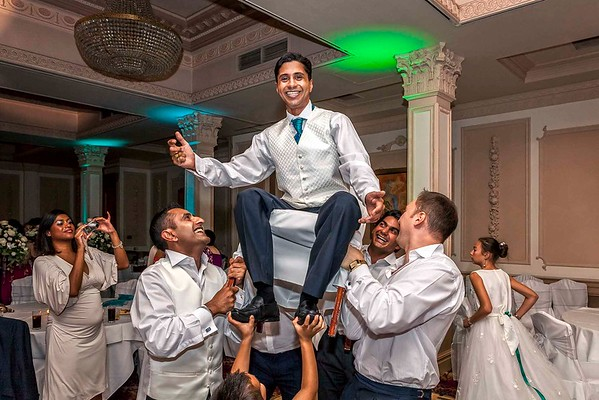 groom lifted into air on chair