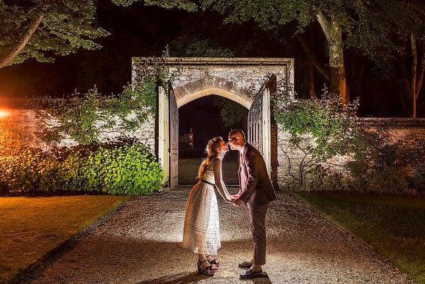 bride and groom kissing in front of gate