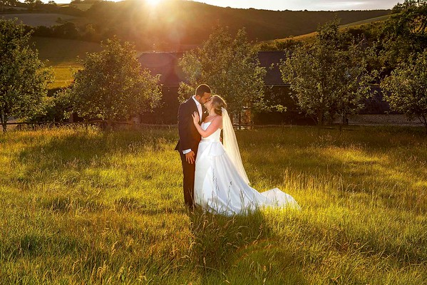 bride and groom in field kissing at sunset